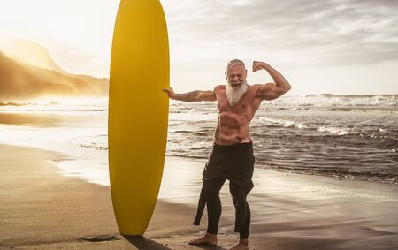 Photo pour Happy fit senior having fun surfing at sunset time - Sporty bearded man training with surfboard on the beach - Elderly healthy people lifestyle and extreme sport concept - image libre de droit