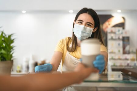 Photo pour Bar owner working only with take away orders during corona virus outbreak - Young woman worker wearing face surgical mask giving coffee to customer - Healthcare and drinks concept - image libre de droit