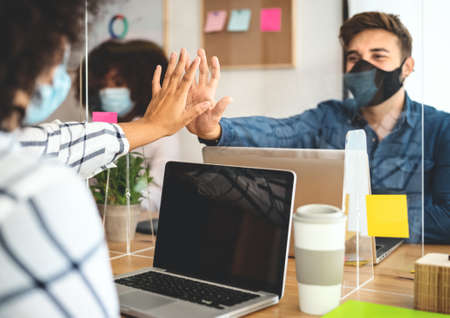 Photo pour Young people in co-working creative space wearing surgical mask protection and keeping social distance to avoid corona virus spread - Health care and business technology concept - image libre de droit