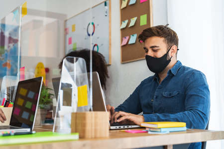 Photo pour Young people in co-working creative space wearing surgical mask and keeping social distance to avoid corona virus spread - Health care and business technology concept - image libre de droit