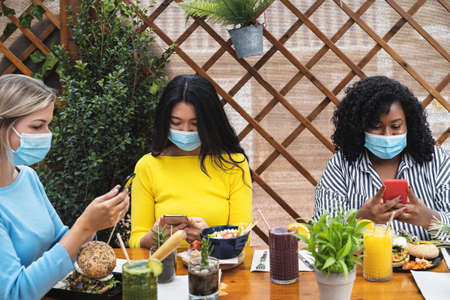 Foto de Multiracial friends using mobile smartphone while having healthy lunch in coffee brunch bar during   virus outbreak - Food and technology concept - Imagen libre de derechos
