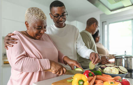 Photo pour Happy African family having fun in modern kitchen preparing food recipe with fresh vegetables - Food and parents unity concept - image libre de droit