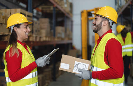 Photo pour Warehouse workers doing inventory using digital tablet and loading delivery boxes plan - Logistic and industry concept - image libre de droit