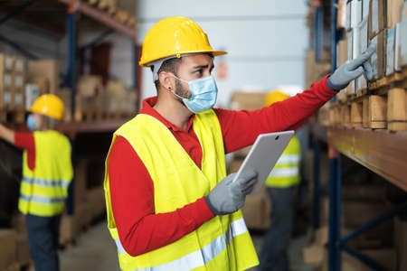 Photo pour Young man working in warehouse doing inventory using digital tablet and loading delivery boxes plan while wearing face mask during corona virus pandemic - Logistic and industry concept - image libre de droit