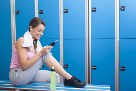 Fitness young smiling woman with towel and bottle using her smart phone with earphones in blue dressing room