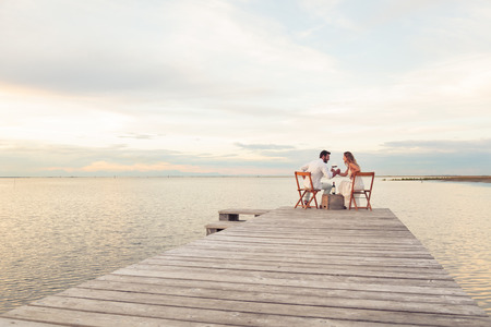 Woman and man couple drinking red wine at the seaside on a jetty