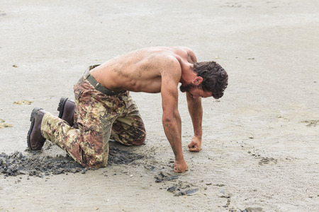 Muscled Shirtless Soldier in Camouflage Pants and Black Shoes Kneeling on the Beach Sand with Fists on the Ground