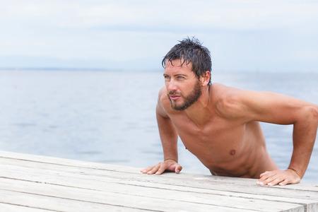 Foto de Close up Portrait of Sexy Confident Handsome Man with No Shirt at the Sea - Imagen libre de derechos