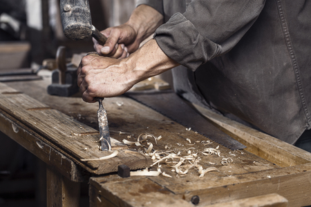 Photo pour Carpenter with a hammer and chisel on the wooden workbench in carpentry - image libre de droit