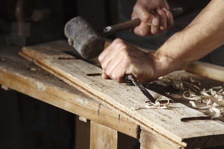 Photo pour Closeup of a carpenter hands working with a chisel and hammer on wooden workbench - image libre de droit
