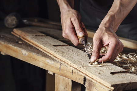Photo pour Closeup of a carpenter hands working with a chisel and carving tools on wooden workbench - image libre de droit