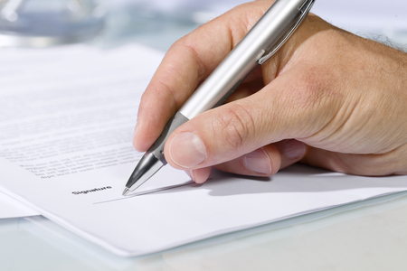 Foto de Close-up shot of hand signing a document with a silver pen. Concept of business and agreement - Imagen libre de derechos