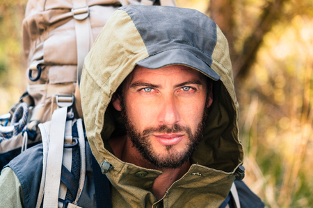 Handsome young man portrait, he is looking at camera. Hooded guy hiking in the forest. Active lifestyle, tourism in nature.