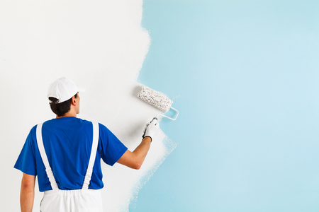 Photo pour Back view of  painter in white dungarees, blue t-shirt, cap and gloves painting a wall with paint roller, with copy space - image libre de droit