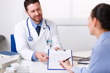 Doctor asking a patient to sign a typed form on a clipboard acknowledging test results, an invoice or consenting to a procedure or admission to hospital