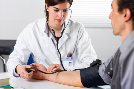 Photo for Portrait Of A Female Doctor Checking Blood Pressure Of Male Senior Patient - Royalty Free Image