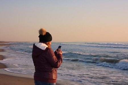 adult woman walks by the sea, on the shoreline, checking her cell phone at sunset