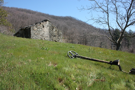 Photo pour a metal detector resting on a lawn, lying on a very green clearing, a field of the Apuan Alps in Tuscany. in front of an abandoned ruin, once a house for farmers and cattle ranchers in the mountains - image libre de droit