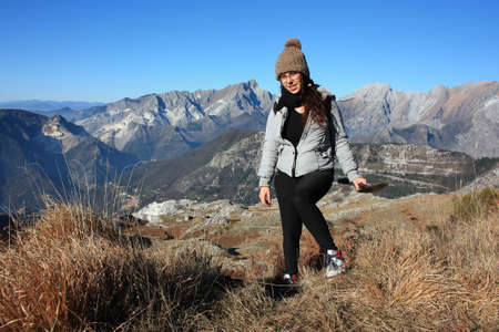 Photo for explorer girl on an adventurous excursion in the mountains of the Tuscan-Emilian Apennines. Apuan Alps on a beautiful sunny cold day - Royalty Free Image