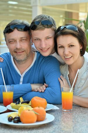 Happy family with son at breakfast on the table