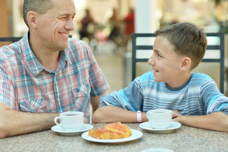 Happy father with son at breakfast on the table
