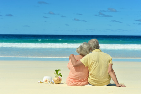 Photo pour Elderly couple sitting on the shore and looks at sea - image libre de droit