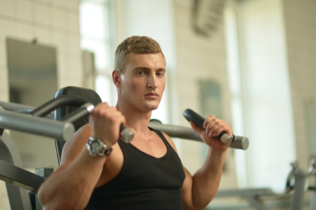 Handsome young man exercises in a gym