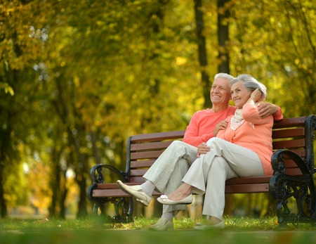 Foto de Happy elderly couple sitting on bench in autumn park - Imagen libre de derechos