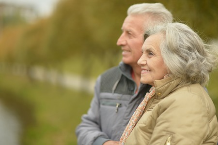 Elderly couple smilling together over natural backgroundの写真素材