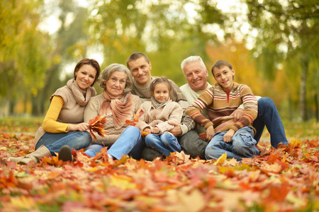 Foto de Portrait of happy family relaxing in autumn forest - Imagen libre de derechos