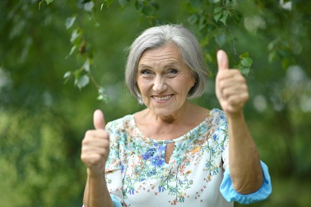Photo for Senior woman showing thumbs up in the park - Royalty Free Image