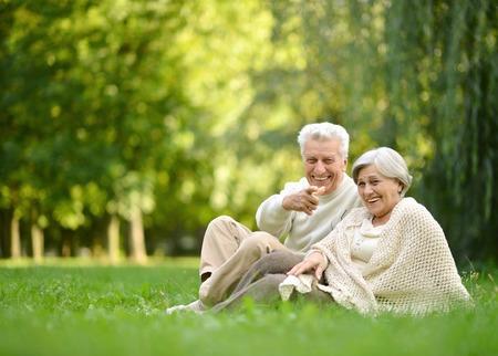 Photo pour Elderly couple sitting together at autumn park grass - image libre de droit