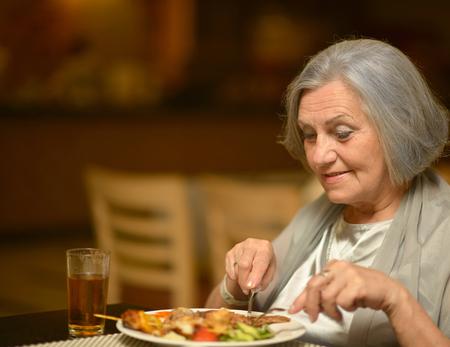 Photo pour Portrait of a happy senior woman eating breakfast at cafe - image libre de droit