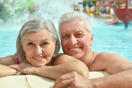 Foto de Senior couple relaxing at pool at hotel resort - Imagen libre de derechos