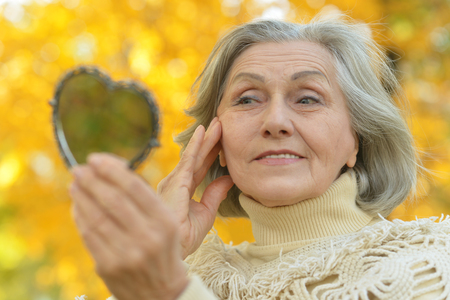 Foto per Portrait of a elderly woman with mirror in autumn - Immagine Royalty Free