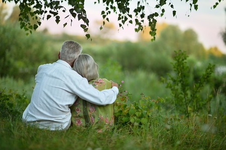 Portrait of happy elderly couple  on nature at summer,back viewの写真素材