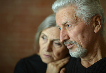 sad Mature couple near wall in the room