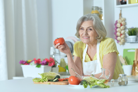 Photo pour Senior woman with grey hair cooking in kitchen - image libre de droit