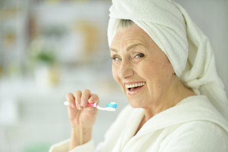 Photo pour elderly woman brushing her teeth in the bathroom - image libre de droit