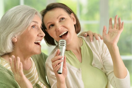 Photo pour Portrait of Senior woman with daughter singing on microphone at home - image libre de droit