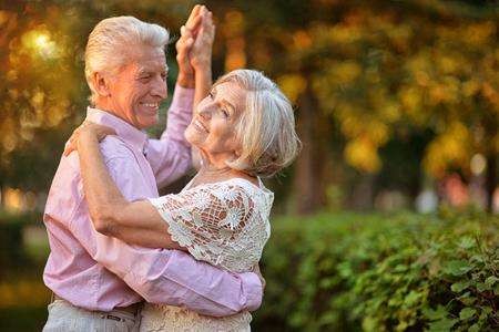 Photo pour portrait of beautiful caucasian senior couple dancing in the park - image libre de droit