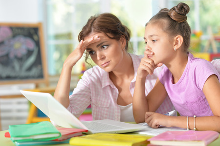 Photo pour Portrait of a mother helping her daughter with homework - image libre de droit