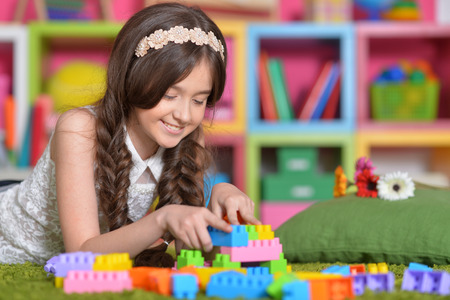 Cute little girl playing with colorful blocks
