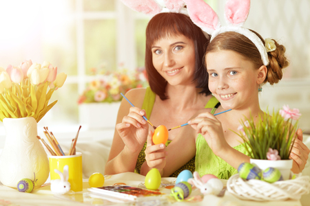 Mother and daughter colouring eggs