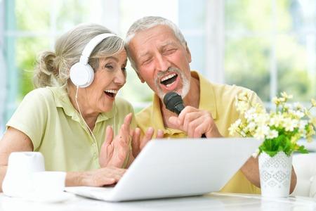 happy senior couple singing karaoke with laptop