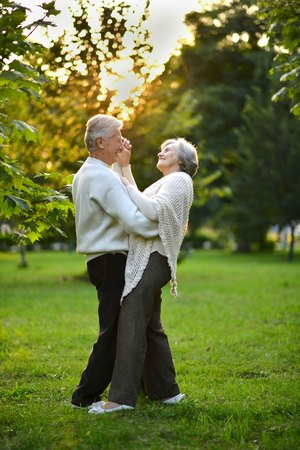 Portrait of old couple dancing in autumn forest