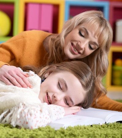Portrait of beautiful mother waking up her little daughter