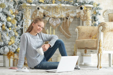 Foto de Portrait of teenage girl using laptop while sitting near Christmas tree - Imagen libre de derechos