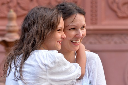 Close up portrait of a mother hugging daughter