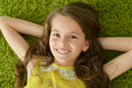 Photo pour Close-up portrait of funny smiling little girl lying on green carpet - image libre de droit
